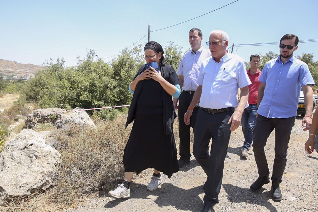 Rina Ariel, the mother of slain teen Hallel Yaffa Ariel, walks with Agriculture Minister Uri Ariel in Kiryat Arba following a terror attack that killed her daughter on June 30, 2016. (Hadas Parush/Flash90)