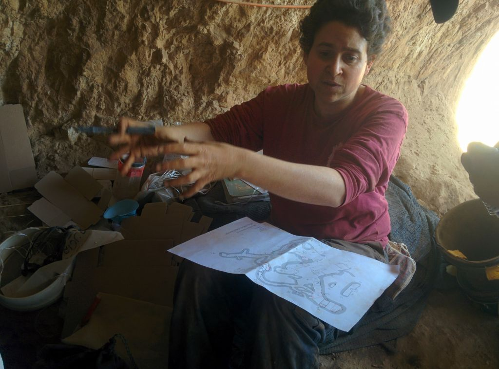 Hebrew University archaeologist Micka Ullman speaks to reporters with a map of the Cave of the Skulls, in the Judean Desert on June 1, 2016. (Ilan Ben Zion/Times of Israel staff)