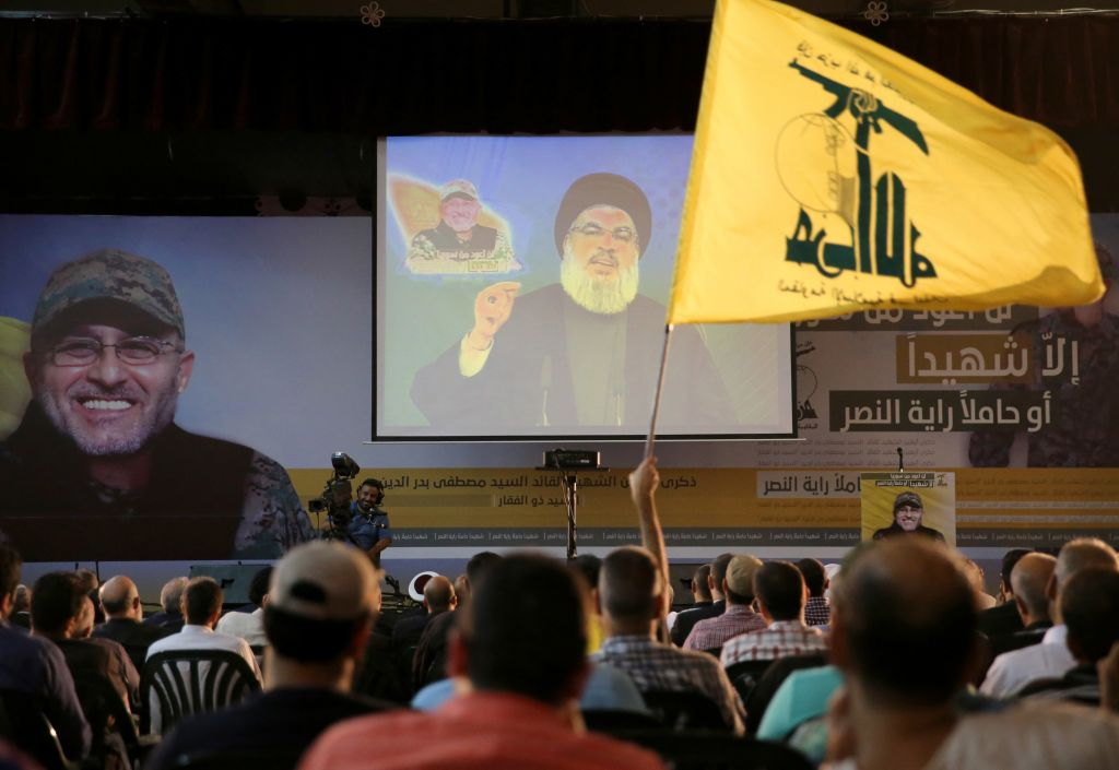 A Hezbollah supporter waves his group's flag, as Hezbollah leader Hassan Nasrallah, center, speaks via a video link, in the southern suburb of Beirut, Lebanon, Friday, June 24, 2016. Nasrallah said the Lebanese Shiite militant group will send more fighters to Syria's Aleppo province, where pro-government forces are battling Syrian rebels on several fronts. (AP Photo/Hussein Malla)