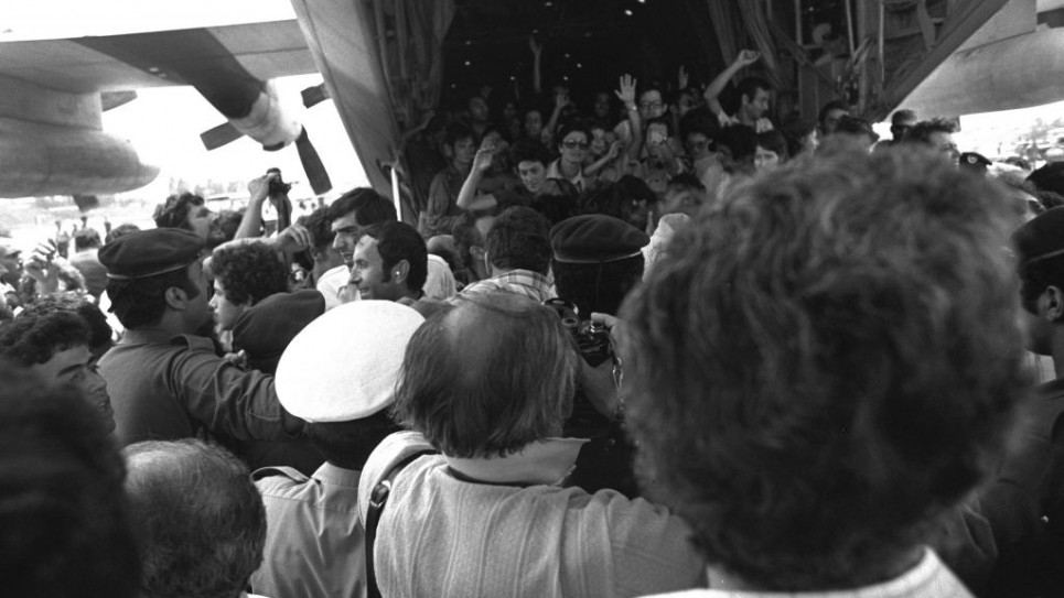 Rescued Air France passengers wave to the waiting crowd while leaving the belly of the Hercules plane at Ben-Gurion Airport.
