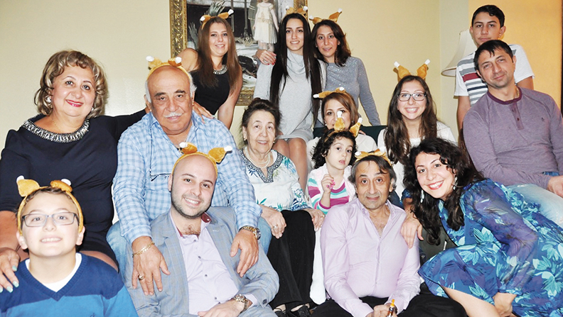 The extended Fatakhov family gathers for Thanksgiving in Forest Hills. In tribute to their dinner, they wear turkey legs — a new family tradition.