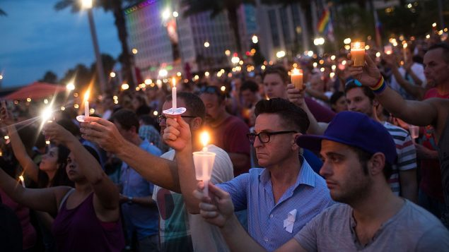 People hold candles at a memorial service for the victims of the Pulse Nightclub shootings in Orlando, Florida. Getty Images