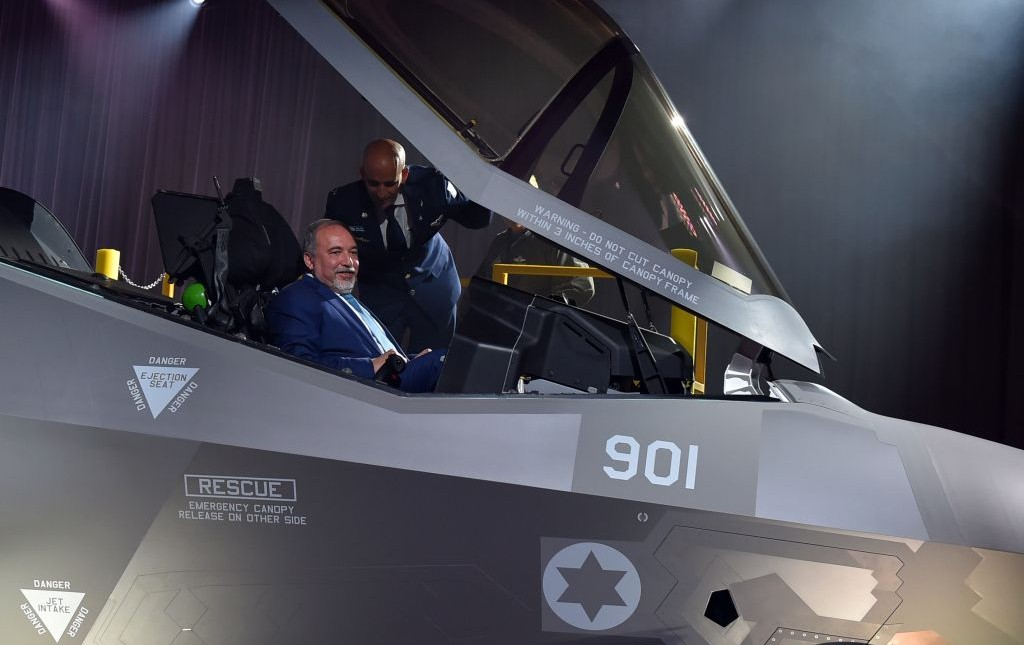 Defense Minister Avigdor Liberman sits in the cockpit of the F-35 stealth fighter jet, as Chief of Staff of the IAF Brig. Gen. Tal Kelman stands over him, during an unveiling ceremony in Fort Worth, Texas, on June 22, 2016. (Ariel Hermoni/Defense Ministry)