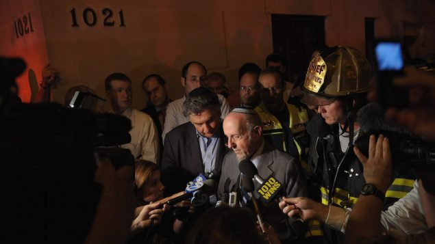Rabbi Haskel Lookstein speaks to the media after a fire damaged the synagogue in 2011. JTA