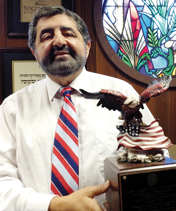 In his office at Temple Beth Sholom of Fair Lawn, Rabbi Alberto Baruch Zeilicovich holds an American eagle the Fort Worth branch of the Jewish War Veterans gave him when he and his family became citizens.
