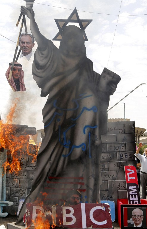 A statute depicting the Statue of Liberty decorated with a Star of David on its head and holding portraits of former British prime minister Tony Blair and Saudi Foreign Minister Adel al-Jubeir is set ablaze by Iranian protesters during a parade marking al-Quds (Jerusalem) Day in Tehran on July 01, 2016. (AFP photo) Tens of thousands joined pro-Palestinian rallies in Tehran, as the annual Quds Day protests take on broader meaning for a region mired in bitter disputes and war. On the bottom R a portrait of Australian born media magnate Rupert Murdoch. / AFP PHOTO / ATTA KENARE