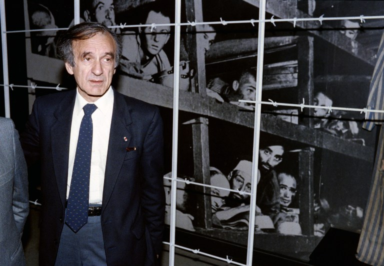 Nobel Peace prize winner and writer Elie Wiesel stands in front of a photo of himself (bottom 3rd from R) and other inmates, taken at the Buchenwald concentration camp in 1945, during his visit to the Holocaust Memorial Center Yad Vashem in Jerusalem, December 8, 1986. (AFP/ SVEN NACKSTRAND)