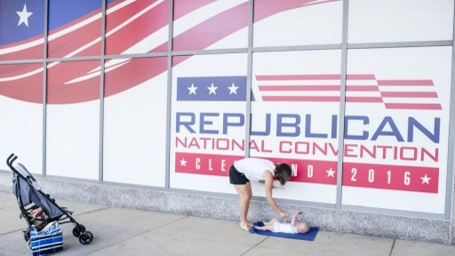 Shannon Holter, a resident of Chagrin Falls, waves an American flag at her six month old son, Ethan, outisde of Quicken Loans Arena on July 11, 2016 in Cleveland, Ohio ahead of the Republican National Convention. (Angelo Merendino/Getty Images/AFP