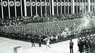 The Olympic Torch-bearer runs through the stadium at the 1936 Berlin Games