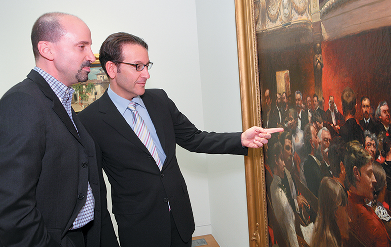 Benjamin Doller, far left, leading an auction; above, at right, he stands with a museum director in 2011 as they discuss a work by the Belgian painter Charles Hermann. It sold for $1 million and now hangs in an Asian museum.