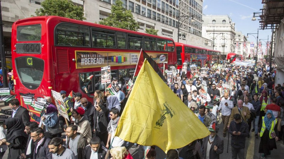 A Hezbollah supporter waves the terror flag in central London during Al Quds Day