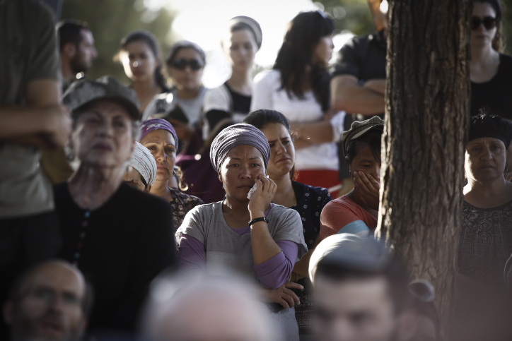 Friends and family members cry during the funeral ceremony for Hallel Yaffa Ariel in the Jewish settlement of Kiryat Arba, in the West Bank, on June 30, 2016. (Yonatan Sindel/Flash90)