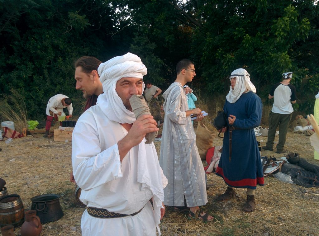 A participant in the annual reenactment of the 1187 Battle of Hattin sips from a can of beer, while another reporter wearing a jalabia interviews another reenactor, on June 30, 2016. (Ilan Ben Zion/Times of Israel staff)