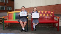 Year 5 pupil Melissa Charles and Liat Tilsiter from Year 2, on the benches which they designed (Photo by James Shaw)