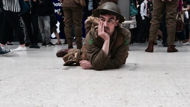 An actor on the Waterloo station platform floor, as part of the 'We are here' project