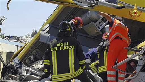 Italian firefighters inspect the wreckage of two commuter trains after their head-on collision in the southern region of Puglia, killing at least 20 people, on July 12, 2016. (Italian Firefighter Press Office via AP)