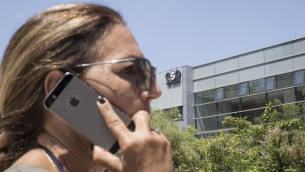 An Israeli woman uses her iPhone in front of the building housing the Israeli NSO group, on August 28, 2016, in Herzliya, near Tel Aviv  / AFP PHOTO / JACK GUEZ