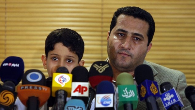 Shahram Amiri, an Iranian nuclear scientist attends a news briefing while holding his son Amir Hossein as he arrives at the Imam Khomeini airport just outside Tehran, Iran, after returning from the United States on July 15, 2010. AP/Vahid Salemi