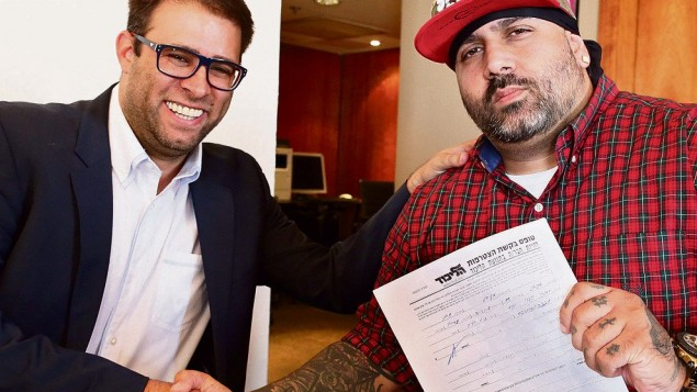 Yoav Eliasi or 'The Shadow' receiving his party papers from controversial MK Oren Hazan.