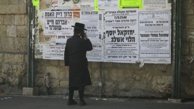 A charedi boy keeps up with the latest rabbinic-sanctioned news via Pashkvilim, public notices. Michele Chabin/JW