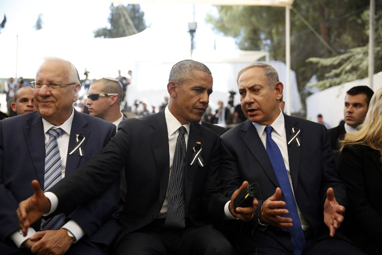 US President Barack Obama, center, speaks to Prime Minister Benjamin Netanyahu, right, as he sits next to President Reuven Rivlin, left, during the funeral of former president Shimon Peres on September 30, 2016, at Jerusalem's Mount Herzl national cemetery. (AFP Photo/Pool/Ronen Zvulun)