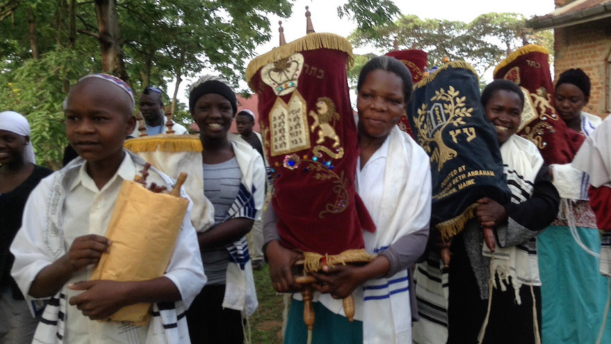 Jewish community members in Nabagoye, Uganda, with the Torah. (Courtesy of Be'chol Lashon via JTA)
