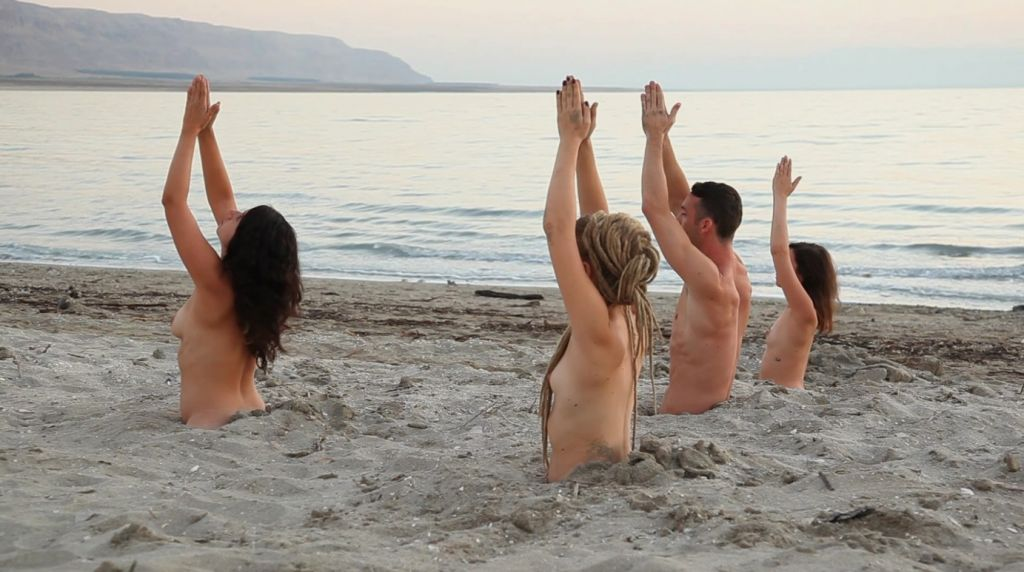 A group of 15 naked models were half-buried in sand for the Dead Sea art installation