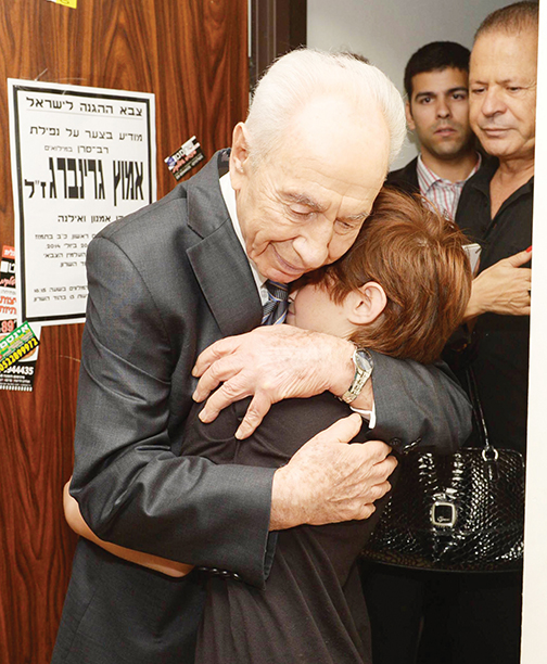 Mr. Peres hugs a mother bereaved as a result of Operation Protective Edge in 2014. (Mark Neiman/GPO)