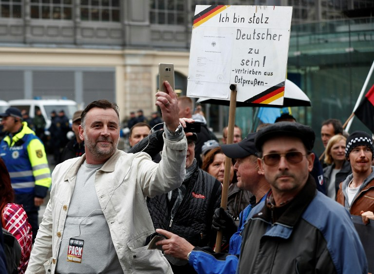 Lutz Bachmann (L), co-founder of the PEGIDA movement (Patriotic Europeans Against the Islamisation of the Occident), documents with his mobile phone as he takes part in a protest against German Chancellor Angela Merkel and her policy, on October 3, 2016. (Odd Andersen)