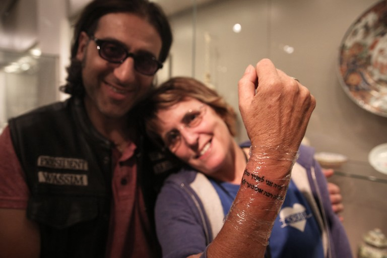 British-Israeli Kay Wilson displays the Hebrew prayer tattoo on her wrist, made by tattoo artist Wassim Razzouk, a Palestinian Christian from Jerusalem's Old City, as part of an initiative to use art to heal both mental and physical wounds at a modern art exhibition hall in the Israeli museum in Jerusalem on October 20, 2016. (AFP PHOTO / MENAHEM KAHANA)