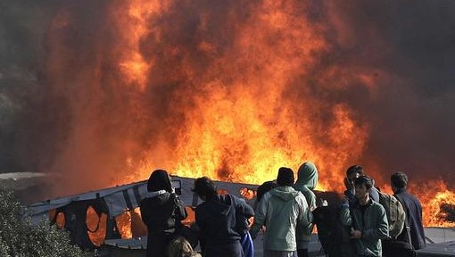 "Thick smoke and flames rise from amidst the tents after fires were started in the makeshift migrant camp known as ""the jungle"" near Calais, northern France, Wednesday, October 26, 2016. Firefighters have doused several dozen fires set by migrants as they left the makeshift camp where they have been living near the northern French city of Calais. (AP Photo/Emilio Morenatti)"