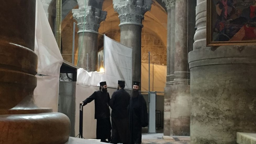 Clergymen outside the Edicule which houses Jesus's tomb at the Church of the Holy Sepulchre in Jerusalem
