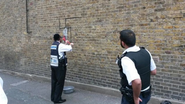 A Shomrim volunteer removing a swastika from a wall in Lower Clapton.