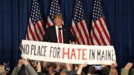 "Republican US presidential candidate Donald Trump smiles as protestors hold up a sign reading ""No Place for Hate in Maine"". RNS"