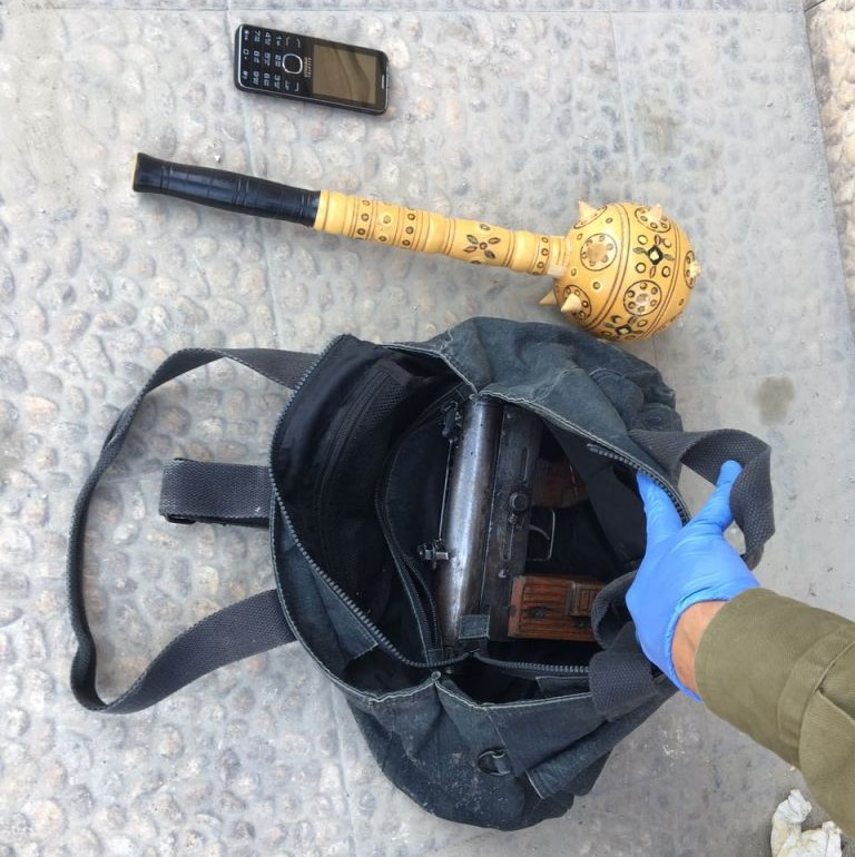 """An IDF soldier inspects a """"Carlo""""-style submachine gun that was confiscated during an arms deal bust, along with what appears to be a wooden mace, in Halhul, outside of Hebron, on October 6, 2016. (IDF Spokesperson's Unit)"""