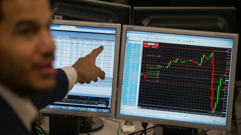 A trader points to a the trading terminal screen showing the S&P 500 Index, as he works at ETX Capital in central London on November 9, 2016, following the result of the US presidential election. (AFP PHOTO / DANIEL LEAL-OLIVAS)