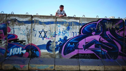A Palestinian boy looks behind a wall separating Jewish part and Palestinian part of the West Bank
