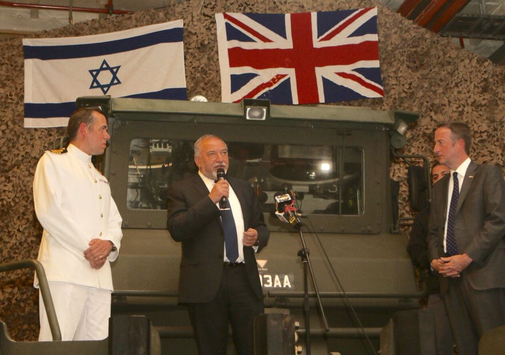 Avigdor Lieberman (centre) speaking underneath Israeli and British flags, with ambassador Quarrey on the right.