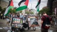Israeli tourists look at a BDS stand with photos and Palestinian flags, calling to 'Free Palestine,' at Dam Square in central Amsterdam, Holland, on June 24, 2016. (Hadas Parush/Flash90)