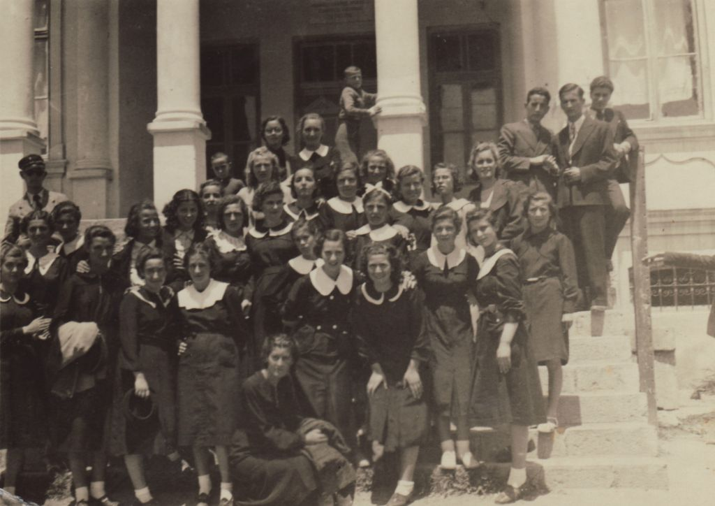 Lena Elias, director Lawrence Russo's mother, in high school in 1938. She is front and center, with a large white collar and her arm around another girl who is leaning down with hands on her knees. (Screenshot)