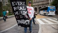 A Donald Trump supporter holds up an anti-Muslim poster at a rally in Cleveland. GETTY IMAGES