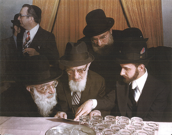 Menachem Genack at his wedding, looking at his ketuba with mentors including Rabbi Soloveitchik