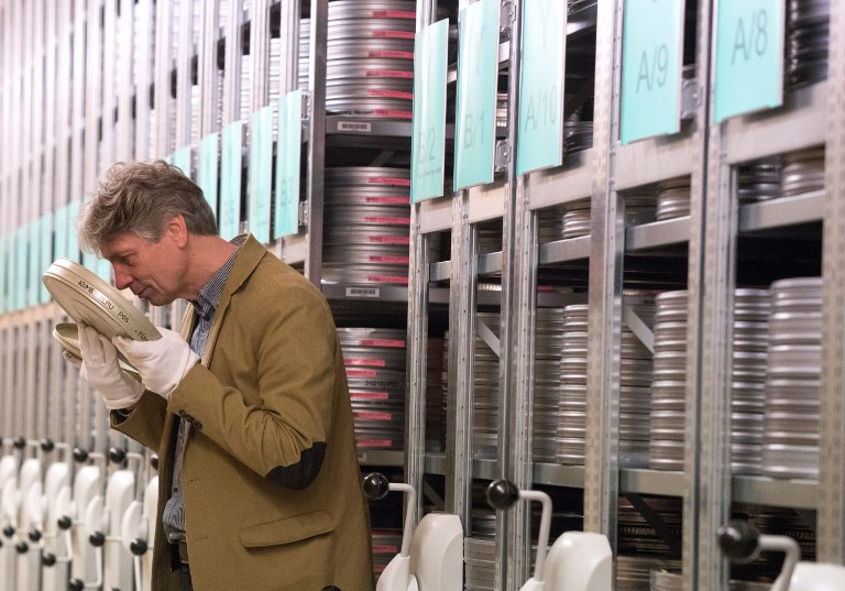 NikolausWostry, head of Film Collections of Filmmarchiv Austria, smells an old film in a special storage at Filmarchive Austria in Laxenburg on November 15, 2016. (AFP PHOTO / JOE KLAMAR)
