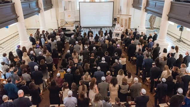 Tamid congregants at Friday evening services. watch the words of prayer that are projected on a screen.PHOTOS COURTESY TAMID
