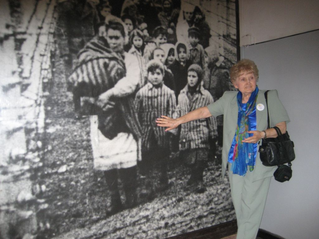Mengele twin Eva Mozes Kor points herself out in an image in the Auschwitz Memorial Museum during a 2007 trip. (courtesy)