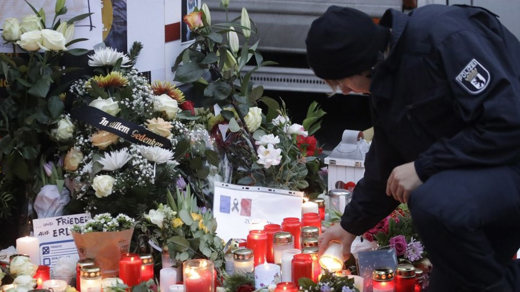 The day after a truck ran into a crowded Christmas market a police officer lights a candle nearby, in Berlin, Germany, December 20, 2016. (AP/Matthias Schrader)