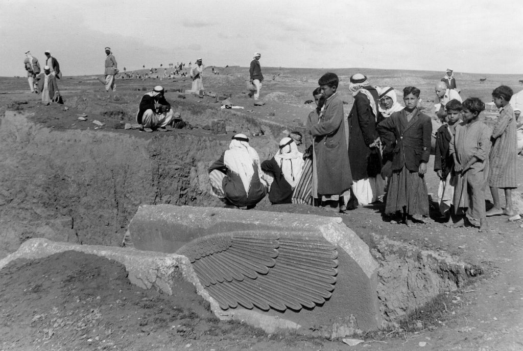 "People gather around the partially-unearthed statue of a lamassu, a great winged bull protective deity, in this undated photo taken by British mystery writer Agatha Christie at the ancient site of Nimrud in northern Iraq. The lamassus at the palace gates were among the works destroyed by IS militants in 2015. Christie's grandson, Matthew Prichard, says she would be heartbroken by the destruction, saying if she and her husband Max Malloran, were alive to see it, ""they would not have recognized the places where they had been and lived and worked."" (Agatha Christie via AP)"