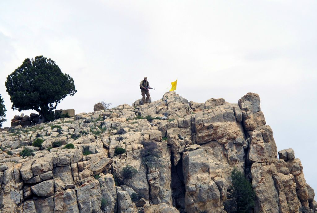 In this Saturday, May 9, 2015 file photo, a Hezbollah fighter stands on a hill next to the group's yellow flag in the fields of the Syrian town of Assal al-Ward in the mountainous region of Qalamoun, Syria. (AP Photo/Bassem Mroue, File)