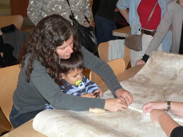 Women's Torah Project artist Aimee Golant, who created the rimonim, and her son, Caleb, sewing the Torah together. (Courtesy Wendy Graff)