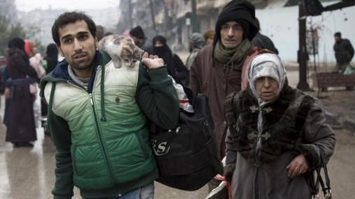 Syrians leave a rebel-held area of Aleppo for the government-held side on December 13, 2016, during an operation by Syrian government forces to retake the embattled city.  (AFP PHOTO / KARAM AL-MASRI)
